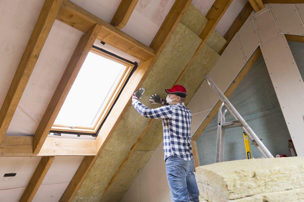 Man isoleert binnenkant dak met isolatiewol