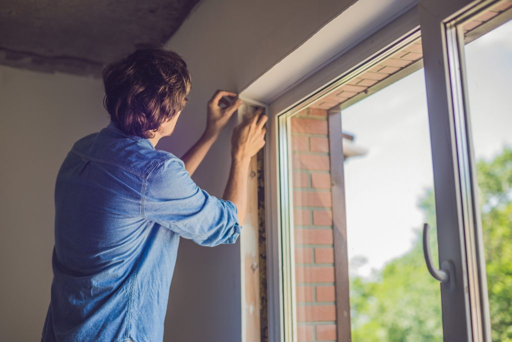 Man plaatst tochtstrips bij raam